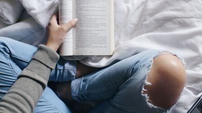 Mulher lendo em cima da cama