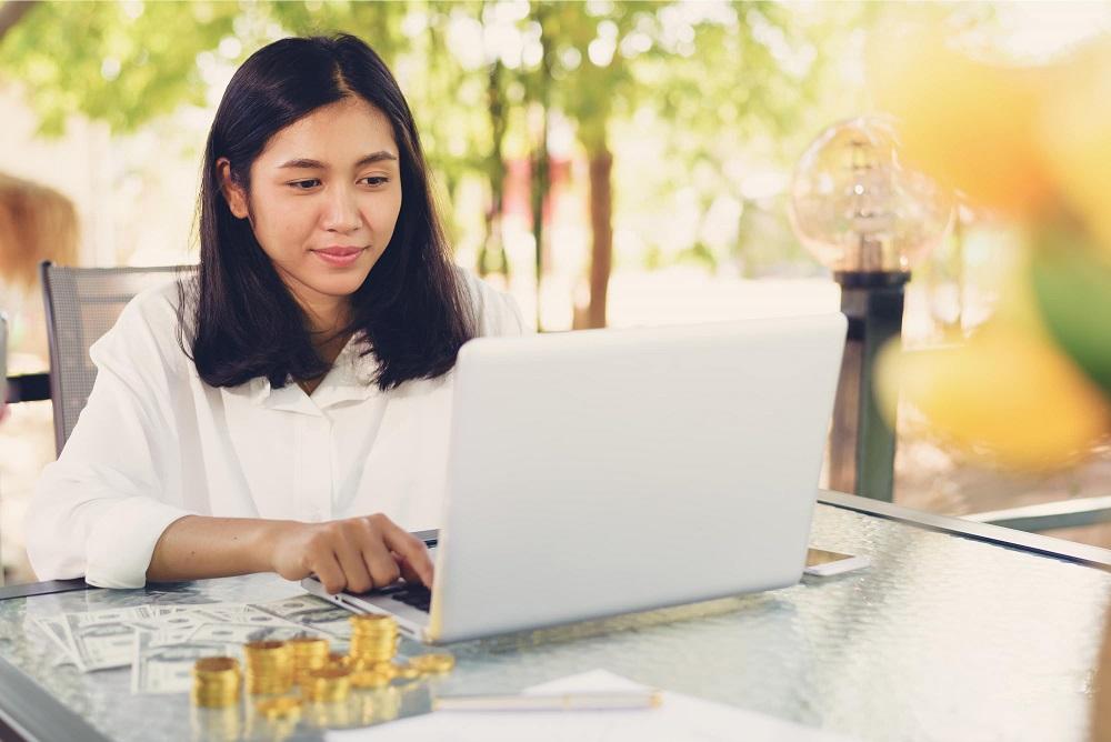 Mulher no computador ganhando dinheiro