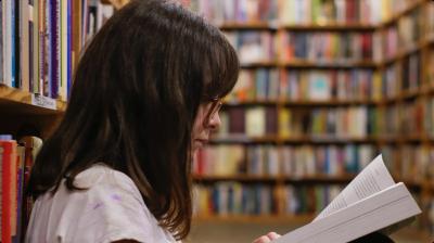 Mulher lendo na biblioteca